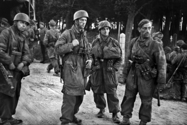German paratroopers assemble on a road in northern France as they prepare to meet the advancing American army, July 1944. In addition to his binoculars and holstered pistol, the soldier at right carries ammunition pouches for an MP40 machine pistol. Their decreasing numbers and the increasing American strength in Normandy meant the days for units such as Fallschirmjäger Regiment 6 were numbered.