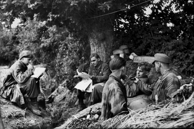 Men of a Fallschirmjäger unit under the cover of a tree in Normandy take time to rest, have a smoke, read a newspaper, and write a letter home before their next encounter with the Yanks.