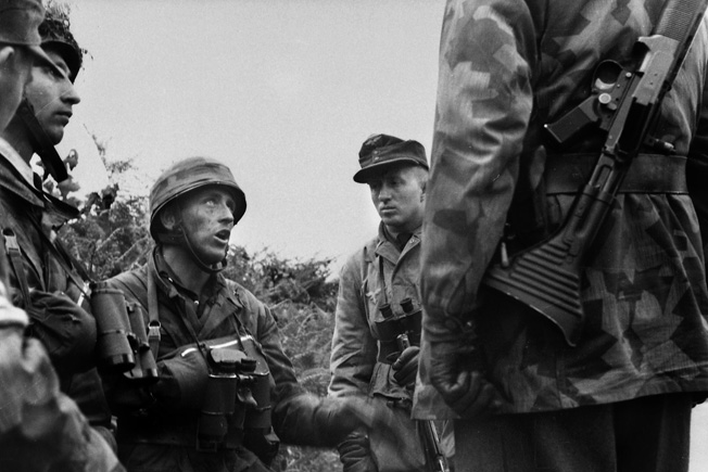 With worried looks, German paratroops try to plan a way to halt, or at least slow down, the American advance near St. Lô. The soldier at right carries a Rheinmetall Fallschirmgewehr Model 1942 (FG42), issued exclusively to paratroops.
