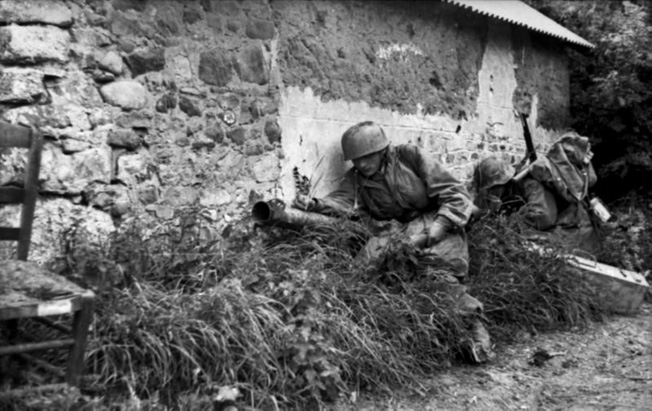 Members of FJR 6 advance along the wall of a French farm building while Allied aircraft pass overhead. The men, part of a tank-killer team, are equipped with a Raketenpanzerbüchse, nicknamed the Ofenrohr (stove pipe).