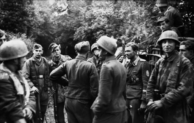 Men of 16th Company, FJR 6, gather around their commander, Oberfeldwebel Alexander Uhlig (right of center, wearing his pilot blouse decorated with medals attached), summer 1944. It was standard practice for German soldiers to wear their medals in combat.