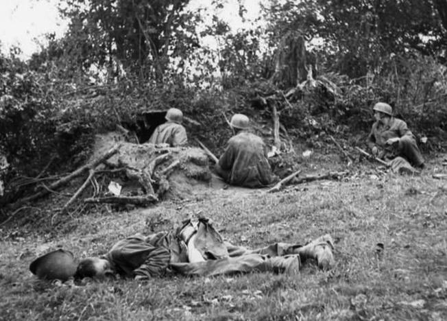 Seemingly unconcerned about the dead American in their midst, members of FJR 6 man a well-concealed defensive position in a Normandy hedgerow.