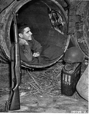 Photographed in a barn near St.-Germain-sur-Séves, this GI from the 90th Infantry Division prepares to get some sleep in an empty wine cask, July 23, 1944.