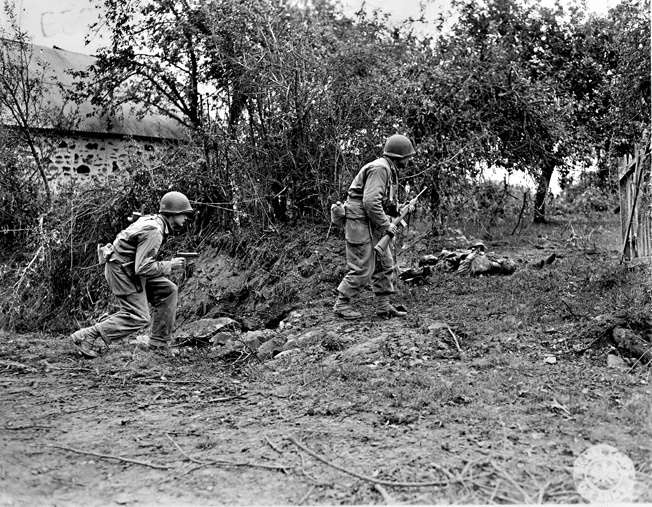 An officer with a carbine and his radioman with a .45-caliber pistol cautiously move past two German corpses during the Allied advance on St. Lô.