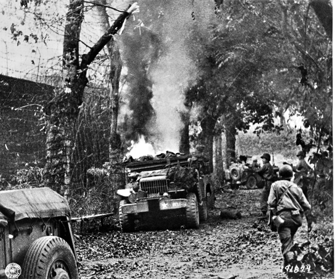 The Germans put up a stubborn defense in Normandy. Here an American Dodge 3/4-ton weapons carrier burns after being hit by enemy artillery near St. Lô, July 20, 1944.