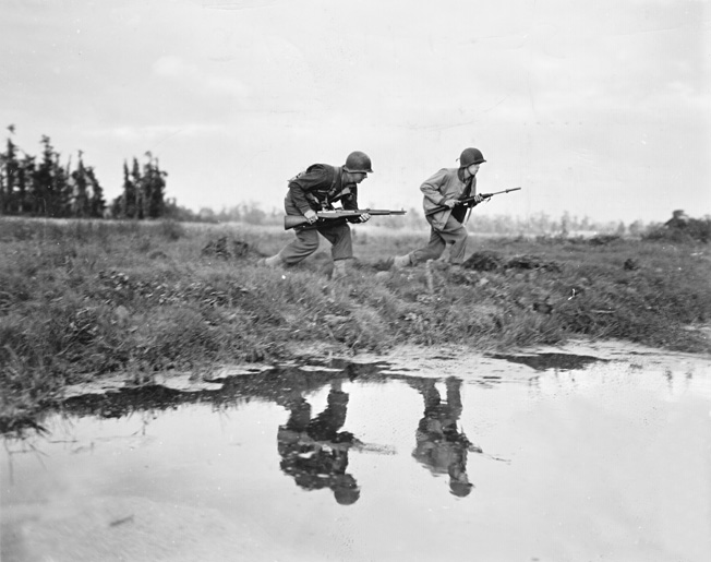 Two Americans, one carrying an M1 Garand rifle and the other wearing a tanker's jacket and carrying an M1 carbine equipped with an M-8 grenade launcher, advance across a French field in pursuit of German paratroopers near St.-Germain-sur-Séves, July 1944.