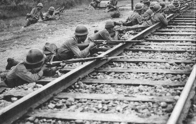 Soldiers of a Japanese rifle company take up positions along a railroad track near Beijing in August 1937.