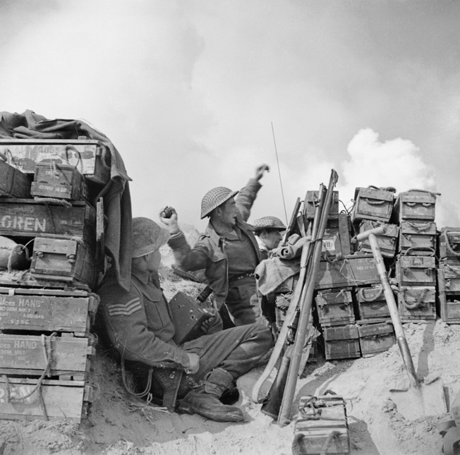 Taking cover behind a stack of ammunition boxes, an infantryman of H Company, 2nd London Irish Rifles hurls a grenade at a German strongpoint on the southern bank of the River Senio, northeast of Bologna, Italy, March 22, 1945.