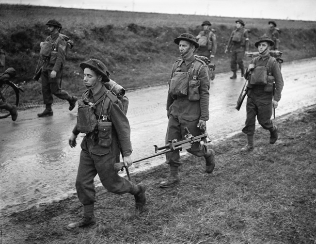 Men of the Royal Irish Fusiliers, part of the British Expeditionary Force sent to France after war was declared, march down a wet road at Gavrelle, near Arras, October 17, 1939. The two men in the foreground are carrying a 14.3mm Boys antitank rifle.