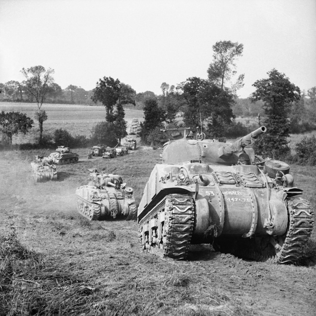 A column of Sherman tanks of 2nd Irish Guards, Guards Armoured Division, advances cross-country south of Caumont, Normandy, France, July 31, 1944.