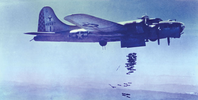 A B-17 bomber from the 69th Bomb Squadron drops a load of fragmentary bombs over a target in Italy. Fitzpatrick had to climb into the bomb bay and pry lose any bombs that failed to drop.