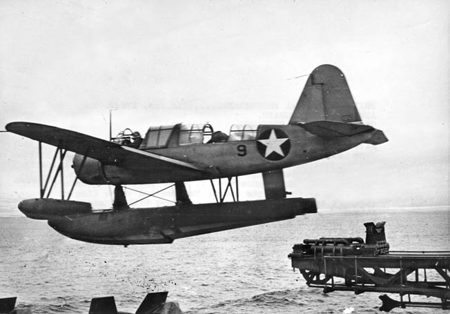 A Vought OS2U Kingfisher scout/observation plane takes off with the assistance of a catapult installed aboard a U.S. Navy Fletcher-class destroyer.