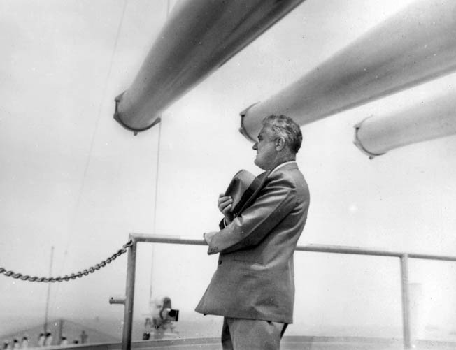 President Franklin D. Roosevelt renders respect to the colors aboard the deck of the cruiser USS Indianapolis during his cruise to South America in November 1936. One of the cruiser's 8-inch gun turrets is visible in the background.