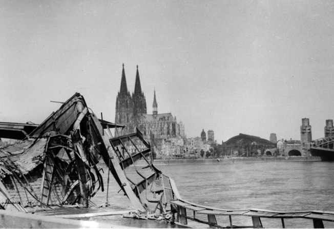 Cologne was bombed 262 times during the war. This photograph (looking west) shows a destroyed bridge over the Rhine River with the Cologne Cathedral (built between 1248 and 1880) in the background. The cathedral was, and is, the largest Gothic cathedral in northern Europe. Although the cathedral did sustain damage, it was not destroyed and was restored in 1956.