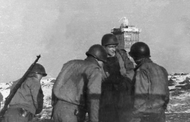 Troops of the 809th gather near the weather station tower (background) atop Brocken Peak, May 1, 1945. (The weather station is near the world's first television transmission and radar tower, built in 1935; it transmitted broadcasts of the 1936 Summer Olympics from Berlin.) The capture of the peak was one of the last battles of the war in the ETO, and was the last combat action for the battalion. Brocken Peak is the highest point in the Harz Mountains (north-central Germany) at an elevation of 3,743 feet. Although other installations on the peak were destroyed in an April 17 Allied bombing raid, the tower survived intact and remains there today.