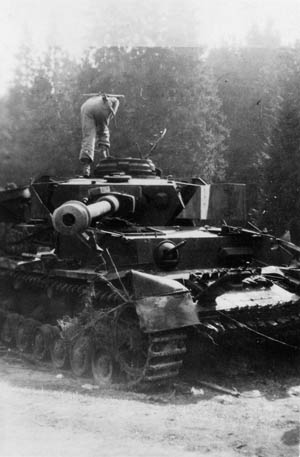 An American peers into the hatch of a knocked-out Panzer IV heavy tank in the Harz Mountains near the town of Schierke, April 29, 1945.