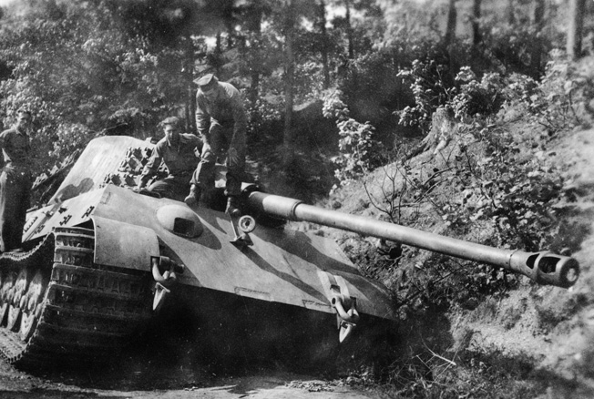 Three GIs inspect a Panzerkampfwagen Tiger Ausf. B (King Tiger, or Königstiger) heavy tank, disabled in the Harz Mountains of north-central Germany near the town of Schierke. Photographed on April 29, 1945.