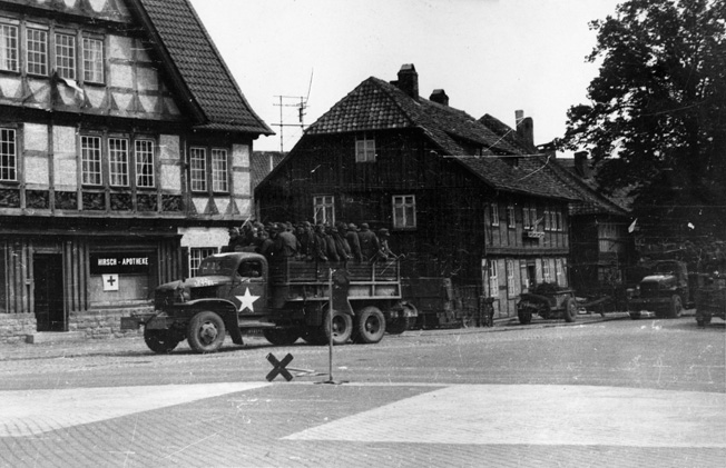 German prisoners of war riding in a 2.5-ton 6x6 truck are being transported to a POW stockade. Photo taken in Wolfenbuüttel, Germany, April 17, 1945.