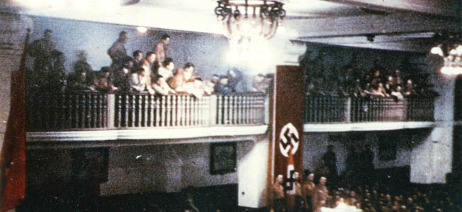 At 8:10 pm, Hitler took his place at the usual lectern, with a Nazi swastika flag covering the pillar directly behind him, six feet away.