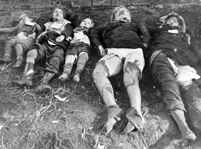 The mulitated corpses of women and children lie gathered for burial in the East Prussian town of Metgethen. Soviet troops were encouraged to exact revenge and retribution for the atrocities suffered in the months that followed the German invasion of the Soviet Union in the summer of 1941.