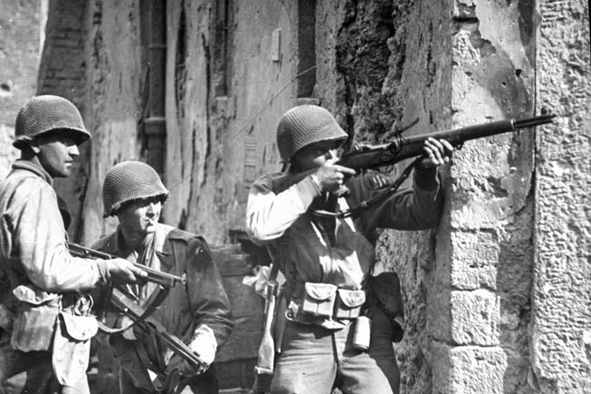 Veterans of the landings and subsequent fighting at Anzio, soldiers of the U.S. 3rd Infantry Division pause at the corner of a house in Cisterna as the lead man takes aim with his rifle at a German sniper some distance away.