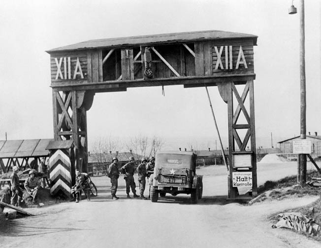 American soldiers stand around the gate of Stalag XII-A, near Limburg, Germany, the prison camp where Ray Miller was held captive in February 1945.