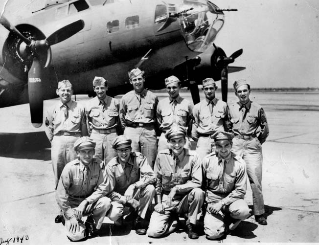 Lieutenant Joe Greasamar poses with other Eighth Air Force members of the 100th Bomb Group. Behind them at an airfield in England sits an icon of the air war over Germany and Occupied Europe, a Boeing B-17 Flying Fortress heavy bomber.