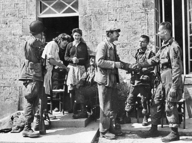 French civilians bring out chairs for troops of the 82nd and 101st Airborne Divisions to enjoy.