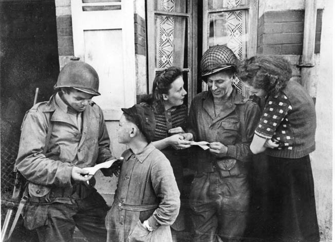 In Isigny, two French women and a boy help American soldiers read French.