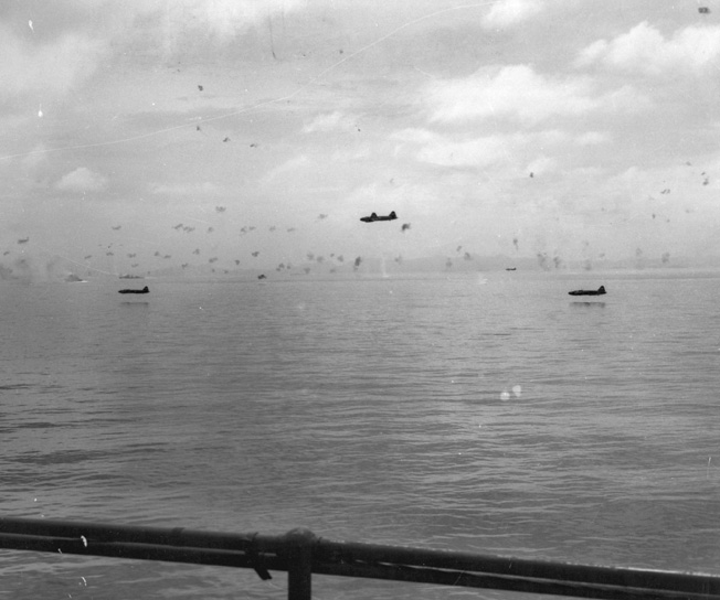 "Japanese Mitsubishi G4M ""Betty"" bombers skim the water during an attack on American transport ships the day after the Marine landing."