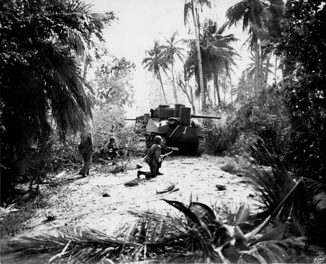 Taking cover behind an advancing M4 Sherman medium tank, American Marines proceed with caution through the Guam jungle. The Sherman was more powerful than any armored vehicle the Japanese could muster, while its 75mm gun also proved its worth against hardened enemy positions.