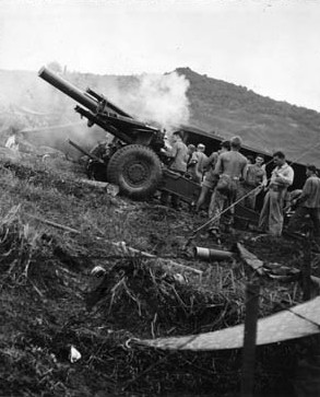 A U.S. Marine Corps howitzer belches smoke during a bombardment of Japanese troop concentrations and machine-gun positions on Guam.