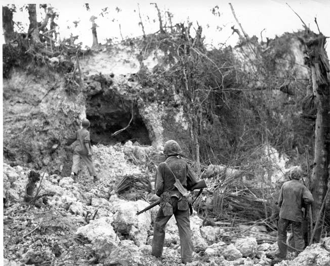 Prior to the American landings on Guam in 1944, the occupying Japanese fortified high ground and took advantage of the natural protection of caves, in which they placed artillery, machine guns, and troop concentrations. In this photo, U.S. Marines cautiously approach a cave opening to confirm that its Japanese occupants are dead.
