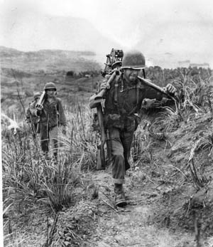 An American machine-gun crew carries its disassembled weapon up a steep hill on the embattled island of Guam in the Marianas. In the foreground, a soldier carries the tripod across his back. He is followed by squad mates carrying the .30-caliber weapon and ammunition along the trail. American Marines and Army troops overcame stiff resistance to retake the U.S. territory from the Japanese in 1944.
