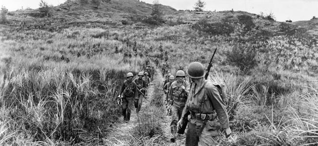 U.S. Army soldiers of Company B, 305th Regiment, 77th Infantry Division advance along a dirt road on Guam. The Army troops experienced delays in landing and heavy enemy fire on the landing beaches.