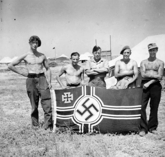 After returning from one of their  trademark covert operations, these SBS men pose proudly with the ensign of the Kriegsmarine,  the German Navy.