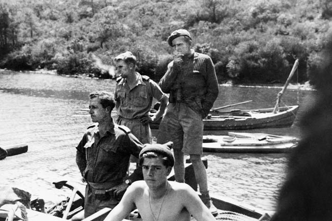 A hero of the SBS, Anders Lassen, who was killed in action late in World War II, stands in the back of a group of his comrades. Several Folboats, the SBS transportation of choice, are seen in the background of this photo.