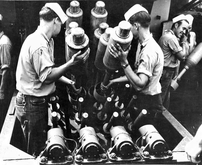 Crewmen aboard a U.S. Navy warship load 24-pound Hedgehog antisubmarine bombs into the projector that was capable of launching them in a circular spread up to 270 yards ahead of the ship. The explosives would detonate only if they struck a target below the surface of the ocean.