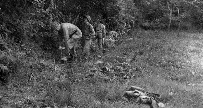 American soldiers dig in along the edge of a hedgerow. The Americans learned quickly to dig in and hug the hedgerows when enemy shelling began.