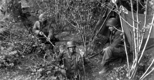American soldiers appear to have staged the mock capture of a German. Although the 26th Infantry Regiment's intelligence officers requested that GIs capture German soldiers for interrogation, the hedgerow country made grabbing them a difficult proposition.