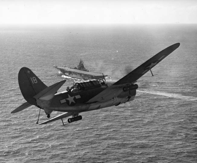 A Curtiss SB2C Helldiver dive bomber approaches a U.S. Navy aircraft carrier. Intended as a replacement for the heralded Douglas Dauntless, the Helldiver proved to be a rugged platform for dive bombing in the Pacific Theater.