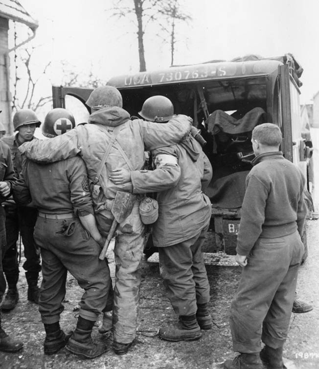 Corpsmen help a wounded soldier of Combat Command B, 12th Armored Division into an ambulance. This man was one of many wounded during the difficult fighting at Herrlisheim on January 9, 1945.