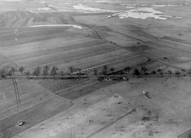 Empty foxholes and destroyed American and German vehicles litter the battlefield around Herrlisheim. This aerial photo was taken a day after the fighting in the area ceased.