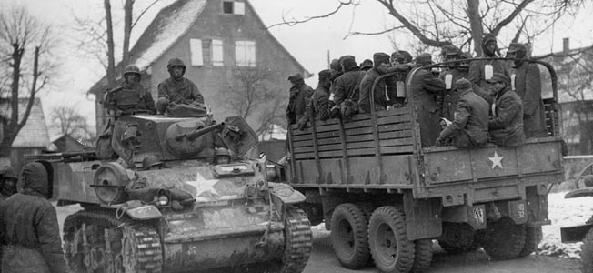 A Stuart light tank of the U.S. Seventh Army moves toward the front line near the border between France and Germany while a truckload of German prisoners heads in the opposite direction.
