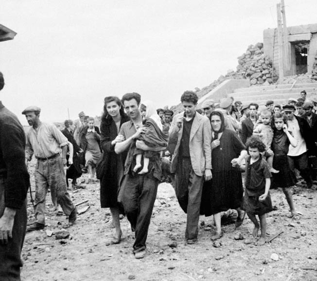 Although shell-shocked by the constant bombardment, Pantelleria's relieved civilians emerge from their shelters. The island's infrastructure was virtually destroyed but, fortunately, civilian casualties were few.