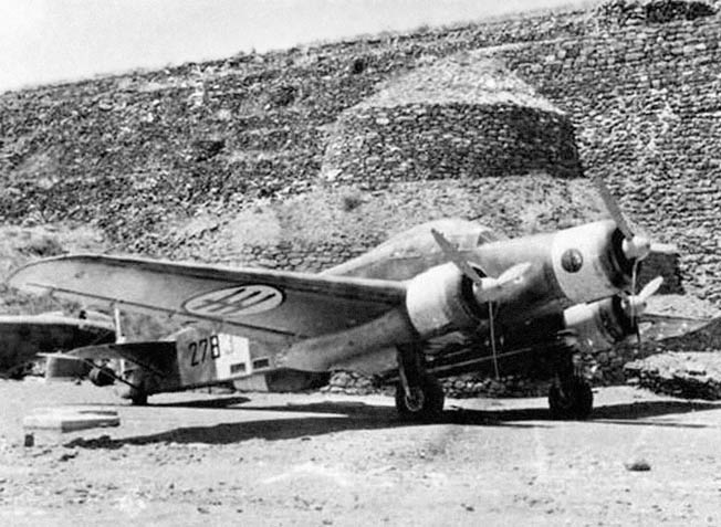 "A Savoie-Marchetti SM.79 ""Sparviero"" medium bomber of the 278th Torpedo Squadron, Regia Aeronautica, parked outside a fortified hangar at Pantelleria's Marghana Airdrome. The SM.79 was considered an excellent, if obsolescent, warplane but, by 1943, stood no chance against Allied aircraft."