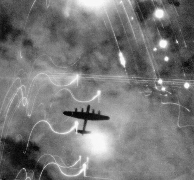 Looking down on a British Lancaster bomber over Hamburg. Fires on the ground and the white streaks of anti-aircraft munitions are clearly visible.