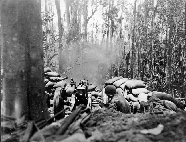 A gunner pulls the lanyard and fires his 75mm pack howitzer through the trees. Smoke from an artillery strike is visible rising from the crest of Hill 260 in the distance.