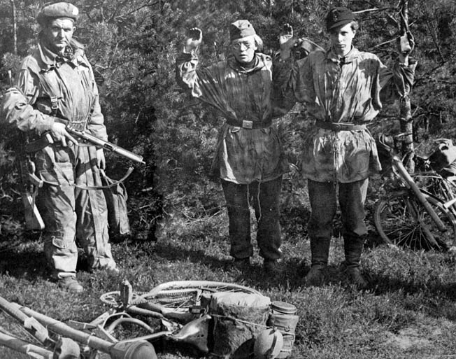 Two members of a Hitler Youth infantry unit trained to attack Allied armored formations stand with their hands up as a British soldier guards them with his Sten gun. The young Nazis were captured while riding bicycles with their Panzerfaust antitank weapons attached. British soldiers were surprised by the youth of many of these combatants.