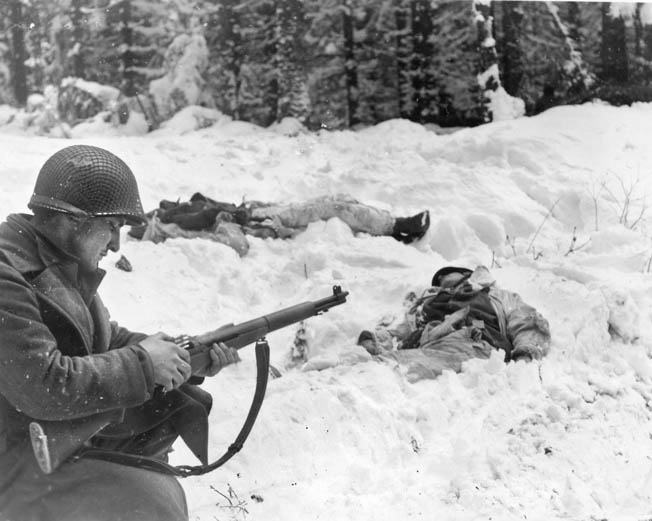 A GI calmly loads his M-1 Garand near two dead Germans whose white camouflage clothing did them no good.